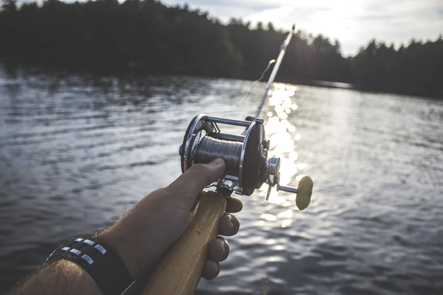 Casting reel on a lake in the summer